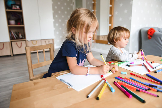 Little boy with sister drawing with felt-tip pens