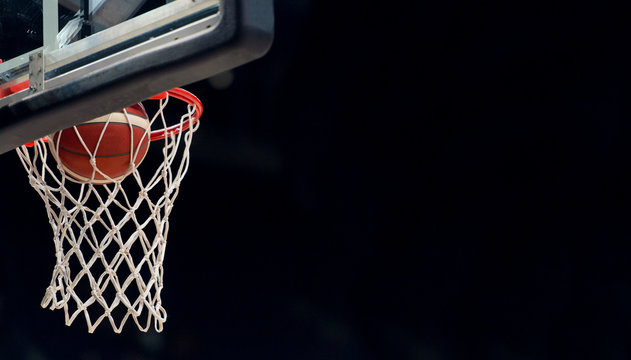 The orange basketball ball flies through the basket