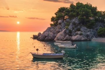 Wall Mural - Beautiful boats on the sea and green trees growing out of the rock at sunset in summer in Croatia. Colorful landscape with motorboats, sandy beach, cliff and orange sky. Travel. Nature background