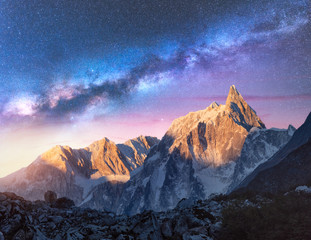 Fototapeta Milky Way over beautiful mountains at night in Nepal. Colorful space landscape with purple starry sky, snowy mountain peak and sunlight at sunrise. Galaxy, stars and high rocks. Travel and nature obraz