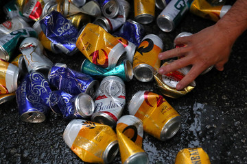 "A recycled waste collector picks up beer cans during carnival block party ""Unidos do Swing"" in Sao Paulo"