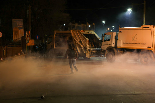 A man runs amid tear gas smoke next to municipal garbage trucks blocking the entrance of the port of Mytilene, before the arrival of a ferry carrying riot police reinforcements sent for monitoring the creation of a new closed migrant detention centre, at