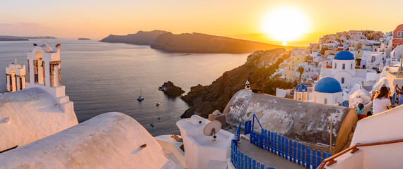 Foto auf Leinwand Santorini Panoramic view of blue domed churches and bell tower with warm sunset light in Oia, Santorini, Greece