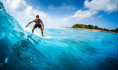 Wall Mural - Young athletic surfer rides the ocean wave on Sultans surf spot in Maldives
