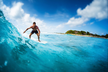 Wall Mural - Young athletic surfer rides the ocean wave on Sultans surf spot in Maldives. Tilt shift effect applied