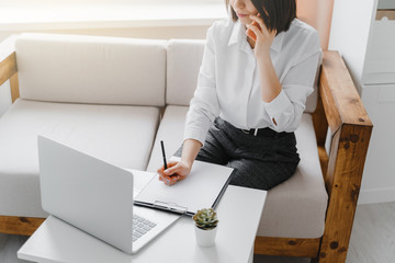 Young business-woman talking on the phone in office or at home. Business concept.