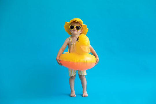 Happy child with yellow rubber duck against blue background