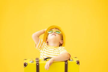 Portrait of happy child with retro yellow suitcase