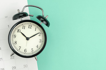 Flat lay or top view  of black alarm clock with white calendar on pastel green background with copy...