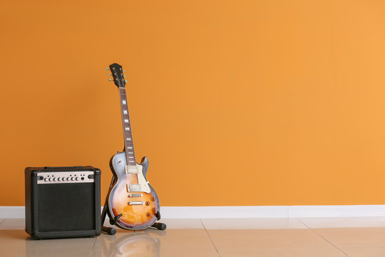 Modern guitar and amplifier near color wall