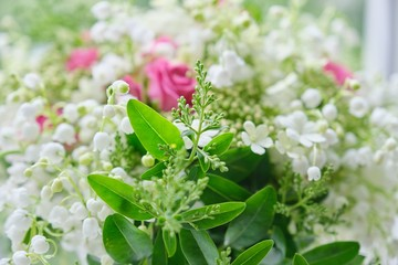 Bouquet of lilies of the valley, pink roses, blooming viburnum