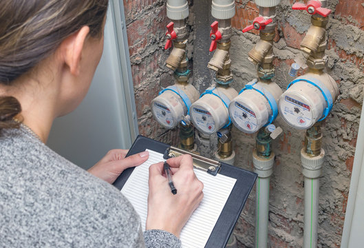 Woman reading the water meter. Household water consumption, concept.