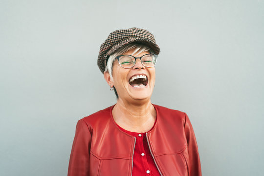 Happy senior woman laughing outdoor - Trendy mature person having fun during retired time - Elderly people lifestyle concept