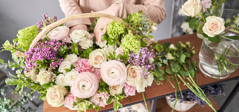 Education in the school of floristry. Master class on making bouquets. Summer bouquet in a wicker basket.. Learning flower arranging, making beautiful bouquets with your own hands. Flowers delivery