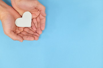 Hands holding a white heart in blue background. Charity, pure love and kindness concept. Top view