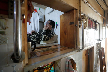 """Simon Wong, 64, smokes a cigarette at his 2 square metre subdivided residential unit, known as a """"coffin home"""", following the outbreak of the new coronavirus, in Hong Kong, China February 17, 2020. Picture taken February 17, 2020. REUTERS/Tyrone Siu"""