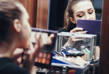 Wall Mural - reflection of a beautiful girl in the mirror doing makeup at the dressing table, young woman preparing face, concept female beauty and cosmetics