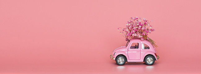 Changxing, China - October 15, 2019: Pink retro toy car delivering bouquet of flowers on white.
