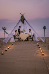 young couple Honeymoon dinner by candle light during sunset on the beach, men and woman having...