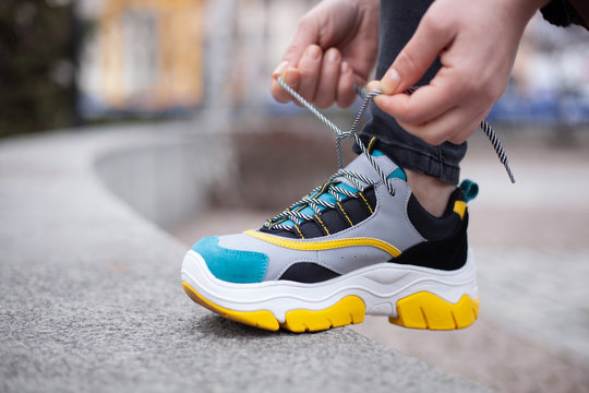 Girl tying shoelaces on multi-colored sneakers of yellow, white, black and blue on the street
