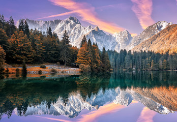 Fotomurales - Impressive Autumn landscape during sunset.  The Fusine Lake in front of the Mongart under sunlight. Amazing sunny day on the mountain lake. concept of an ideal resting place. Creative image.