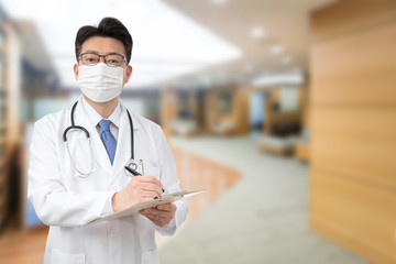 An Asian male doctor holding a medical chart at the hospital while wearing a mask