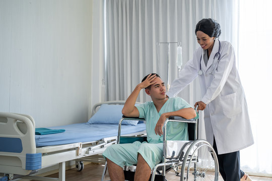 The african american doctor is pushing the wheelchair And provide consultation regarding treatment to patients sitting in a wheelchair and closely monitor