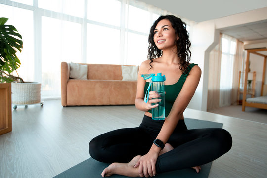 Beautiful Hispanic woman with bottle of water sitting on yoga mat at home, empty space