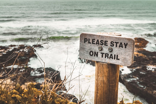 Please Stay on Trail wooden signpost along the Pacific Coast, Cape Perpetua, Yachats, Oregon, USA.