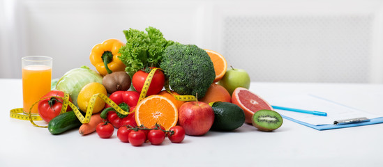 Nutritionist's workplace with fruits, vegetables, measuring tape on table