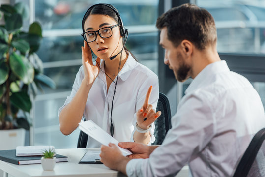 professional asian translator working online with headset while having meeting with businessman