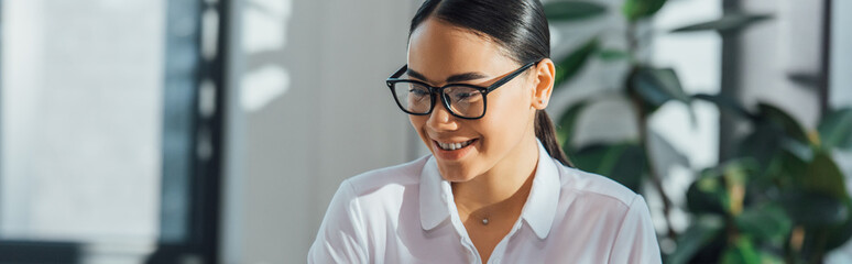 panoramic shot of asian translator in eyeglasses working in office Fotomurales