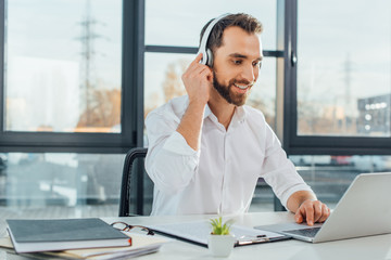 professional cheerful translator working online with headphones and laptop in office Fotobehang