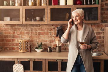 Relaxed Aged Lady With Cellphone And Wine Glass In Kitchen Interior Wall mural
