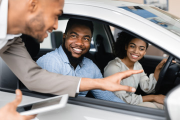 Joyful Couple Buying Car Talking With Salesman In Dealership Store