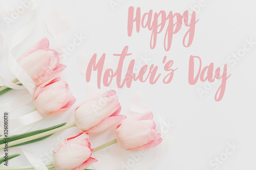 Happy mother's day.  Happy mothers day text and pink tulips floral border on white background. Stylish soft image. Floral Greeting card. Happy Mothers day. Handwritten lettering