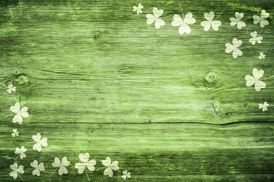 Shamrocks on green wooden table a symbol og St. Patricks Day. Bbanner with corner border of shamrocks.Textured pattern.