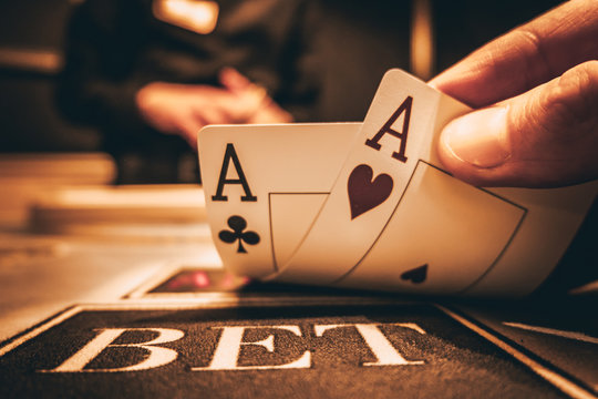 Dealer or croupier shuffles poker cards in a casino on the background of a table, chips. Concept of poker game, game business. Playing for money, a big win, a jackpot, gambling, a desire to get rich.