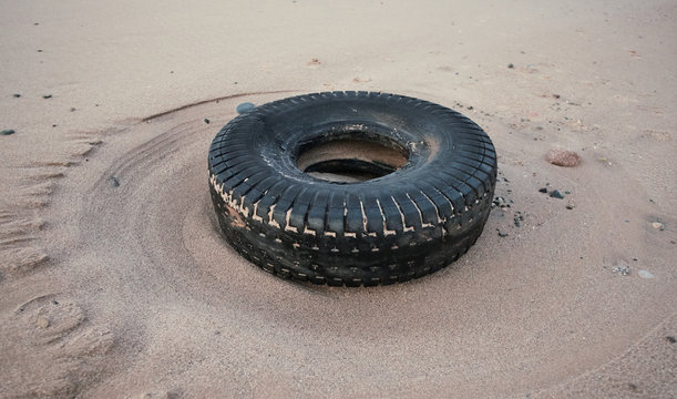 rubber dirty old vehicle tyre washed up on a sandy luxurious beach destination. Environmental plastic pollution issue causing world  news. Health disaster on beaches.