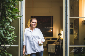 Portrait of female design professional standing at house entrance