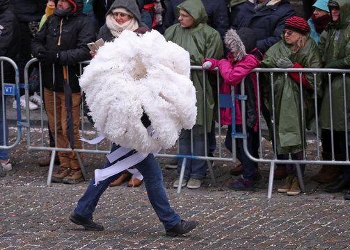 """A man carries an ostrich feather adorned hat worn by the """"Gilles of Binche"""" performers during the Binche carnival,"""