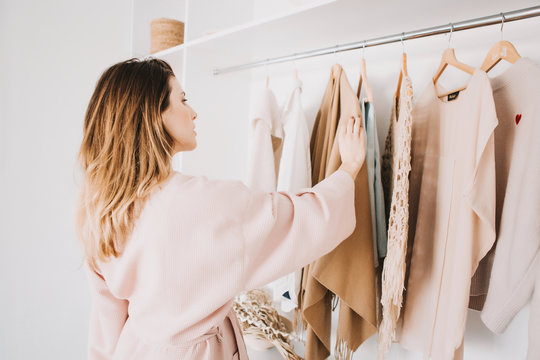 Cute young woman standing in front of hanger rack and trying to choose outfit.