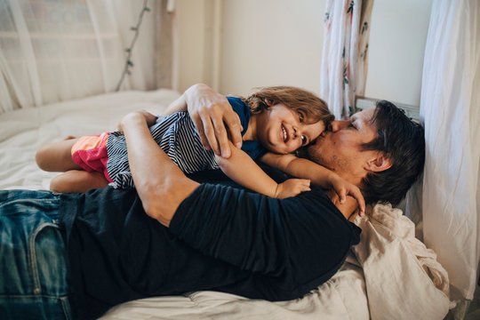 Mature father kissing his daughter while lying on bed