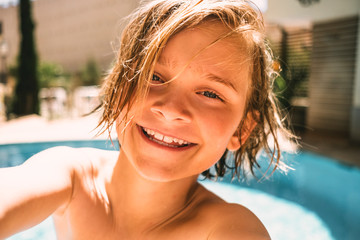 Portrait of smiling boy by swimming pool in resort