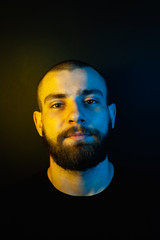 Portrait of a hipster guy with color light. Hipster face portrait in studio.