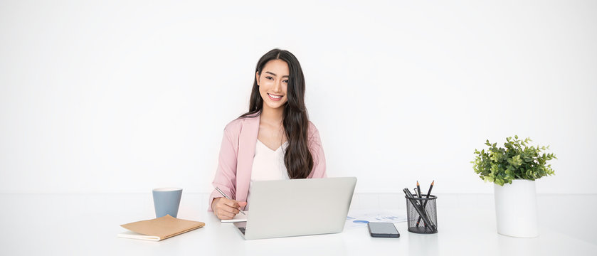 Portrait of smiling beautiful business asian woman in pink suit working in home office desk using computer. Business people employee freelance online marketing e-commerce, work from home concept