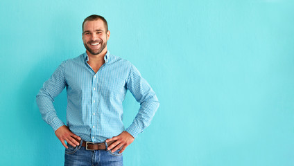 Happy man in front of blue wall with copy space