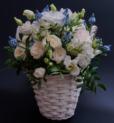Tuinposter Lelie Bouquet. Composition of fresh, delicate flowers in a white basket against a dark background.