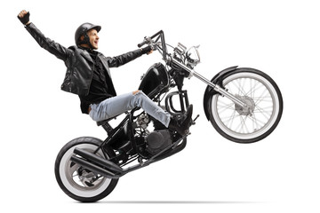 Happy young male biker riding a custom motorbike with one wheel up and gesturing with hand