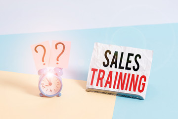 Writing note showing Sales Training. Business concept for train salesshowing the methods of great sales techniques Alarm clock beside a Paper sheet placed on pastel backdrop